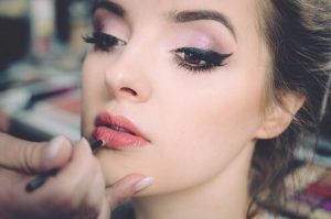 Model applying lipstick | Prestons Beauty Academy